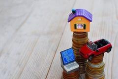 Casa do carro do computador na pilha das moedas do dinheiro foto de stock royalty free