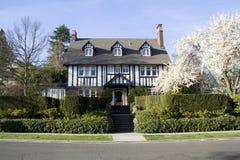 Casa do estilo tradicional com jardim da frente bonito fotografia de stock