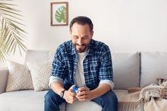 Casa do homem apenas que senta-se no sofá que faz a combinação no cubo dos rubik alegre foto de stock royalty free