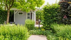 Casa do jardim em um jardim colorido com pátio Fotografia de Stock Royalty Free
