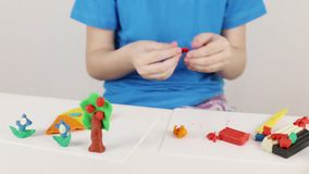 Casa do molde de mãos da menina, árvore, flores do plasticine na tabela na sala video estoque