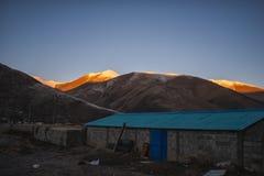 Casa do nascer do sol da montanha da neve sob a montanha imagens de stock royalty free