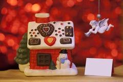 Casa do Natal com anjo no fundo vermelho fotografia de stock