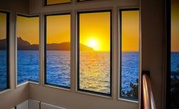 Casa do por do sol do oceano da janela Fotografia de Stock