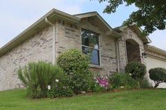 Casa do tijolo com o jardim em suburbano imagens de stock