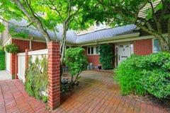 Casa do tijolo exterior com jardim da frente do assoalho de telha Imagem de Stock Royalty Free