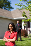 Casa: Donna con l'agente immobiliare Behind Fotografie Stock