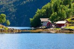 Casa e cabanas na costa do fiorde de Bergen. Imagem de Stock