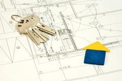 Casa e chaves sobre plantas da construção Fotografia de Stock Royalty Free