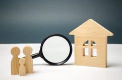 Casa e lupa de madeira com família Avaliação da propriedade Escolha de lugar para a construção Pesquisa da casa fotos de stock royalty free