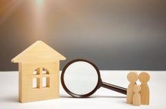 Casa e lupa de madeira com família Avaliação da propriedade Escolha de lugar para a construção Pesquisa da casa foto de stock royalty free