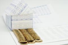 Casa e muitas pilha de moedas de ouro Fotografia de Stock