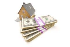 Casa e pile di soldi isolate Fotografia Stock
