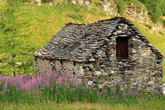 Casa e prado de pedra velhos nos cumes italianos Imagens de Stock