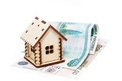 Casa e soldi di legno su un fondo bianco Fotografia Stock