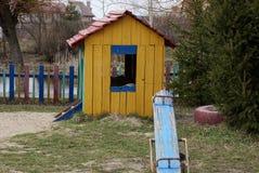 Casa ed oscillazioni dei bambini sul campo da giuoco nell'esterno dell'erba fotografia stock libera da diritti
