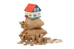 Casa em sacos com moedas Fotografia de Stock Royalty Free