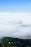 Casa em um monte com o mar das nuvens Fotos de Stock Royalty Free