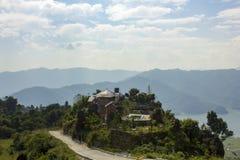 Casa em um monte verde na perspectiva das silhuetas de um vale da montanha na névoa imagem de stock