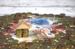 Casa en billetes de banco y monedas euro Fotografía de archivo