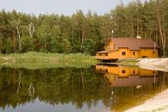 Casa en el bosque sobre el lago Foto de archivo libre de regalías