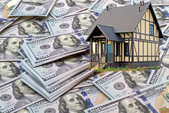 Casa en el fondo de billetes de banco cientos dólares Foto de archivo libre de regalías