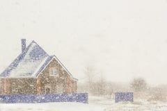 Casa en el fondo de nevadas abundantes Foto de archivo