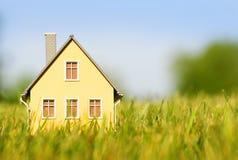 Casa en hierba verde sobre el cielo azul hipoteca Fotos de archivo