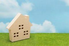 Casa en hierba verde sobre el cielo azul y las nubes Imagenes de archivo
