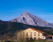 Casa en la colina y la montaña fotos de archivo libres de regalías