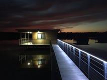 Casa en la reflexión de la puesta del sol del lago en noche ny del agua foto de archivo libre de regalías