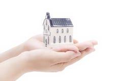 Casa en las manos, conceptos de la economía de las propiedades inmobiliarias Fotografía de archivo libre de regalías