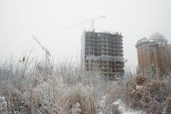 Casa en las ramas de los árboles cubiertos con la grúa backgroundBuilding de la helada y el nuevo edificio bajo construcción en e Imagen de archivo