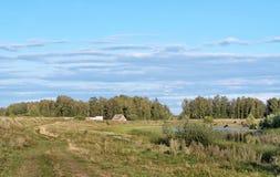 Casa en orilla del pequeño lago en el verano Imagenes de archivo
