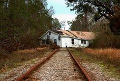 Casa en pistas de ferrocarril fotografía de archivo