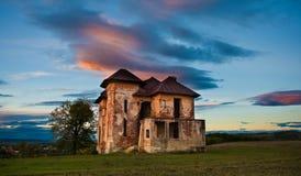 Casa encantada y cielo abandonados viejos en Transilvania con las nubes Foto de archivo libre de regalías