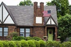 Casa encantador do tijolo com a porta ajardinar e de verde-lima com grinalda e voo da bandeira americana com árvores luxúrias atr Fotografia de Stock