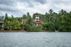 A casa entre a selva no banco de rio Fotos de Stock