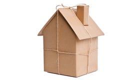 Casa envuelta en el papel marrón cortado Imagenes de archivo