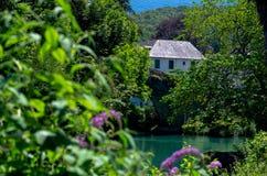 Casa escondida pelo rio Fotos de Stock Royalty Free