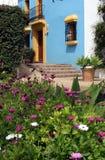 Casa española en pueblo con las paredes azules y el ajuste amarillo Imagenes de archivo