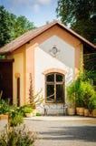 Casa estiva per la roba di giardinaggio con le piante nella parte anteriore Immagini Stock