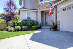 Casa exterior com entrada de automóveis e a bandeira americana. Imagens de Stock
