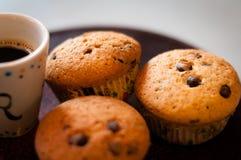 Casa fatta Cioccolato Chip Muffins con una tazza di caffè immagine stock libera da diritti