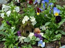 Casa feericamente pequena no canteiro de flores da viola Fotografia de Stock