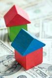 Casa feita dos blocos de madeira do brinquedo no fundo do dólar Imagens de Stock