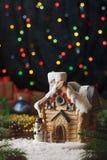 Casa festiva del juguete de Navidad con el muñeco de nieve en fondo de la oscuridad de la guirnalda Foto de archivo
