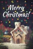 Casa festiva del juguete de Navidad con el muñeco de nieve en fondo de la oscuridad de la guirnalda Imagen de archivo