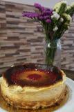 A casa fez o bolo de queijo e as flores imagens de stock