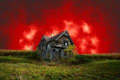 Casa frecuentada asustadiza de Halloween con el cielo rojo malvado Imágenes de archivo libres de regalías